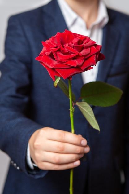 Un adolescente tiene in mano una rosa rossa. il ragazzo è vestito con un abito blu e una camicia bianca. avvicinamento. Foto Premium