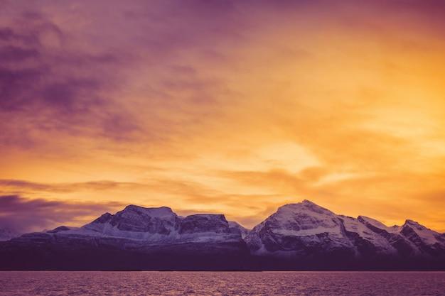 Un'alba di fuoco sulle cime innevate del fiordo Foto Premium