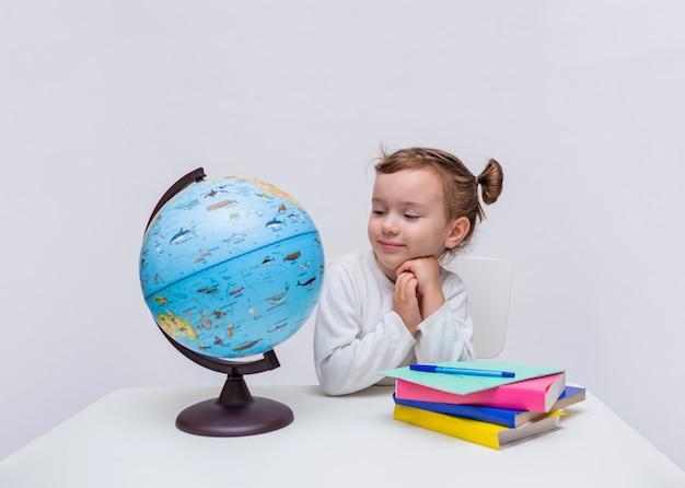 Un allievo bambina si siede a un tavolo con un globo e libri e guarda la telecamera su un bianco isolato Foto Premium