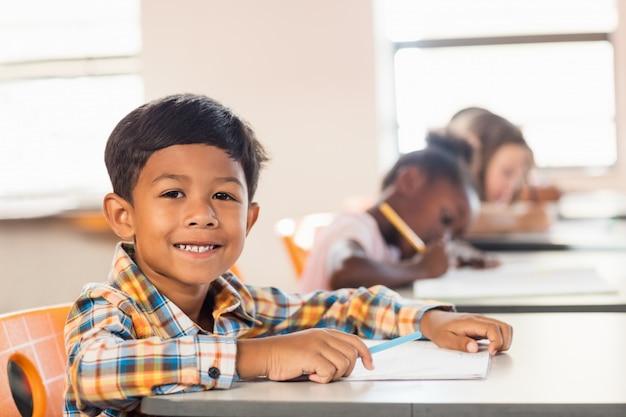 Un allievo carino in posa sulla sua scrivania Foto Premium