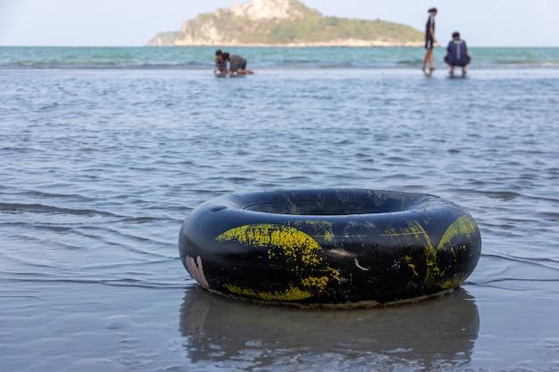 Un anello di nuotata nero su una spiaggia di sabbia dell'oceano Foto Premium