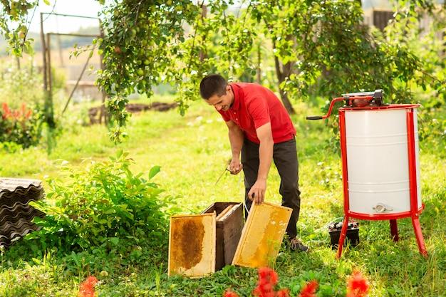 Un apicoltore con una cuffia protettiva lancia in opera un estrattore di miele nella fattoria delle api Foto Premium