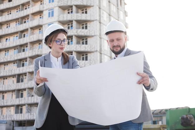 Un architetto di due professionisti che tiene il modello e che lo esamina vicino al cantiere Foto Gratuite