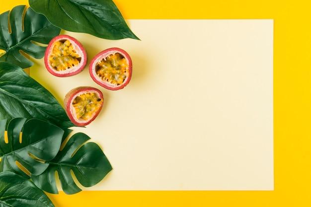 Un artificiale lascia con frutto della passione contro la carta bianca su sfondo giallo Foto Gratuite