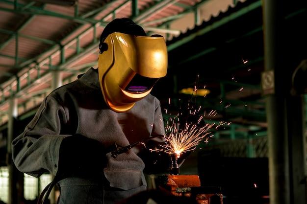 Un artigiano sta saldando con l'acciaio del pezzo in lavorazione Foto Premium