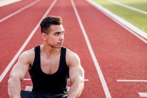 Un atleta di sesso maschile seduto sulla pista da corsa guardando lontano Foto Gratuite
