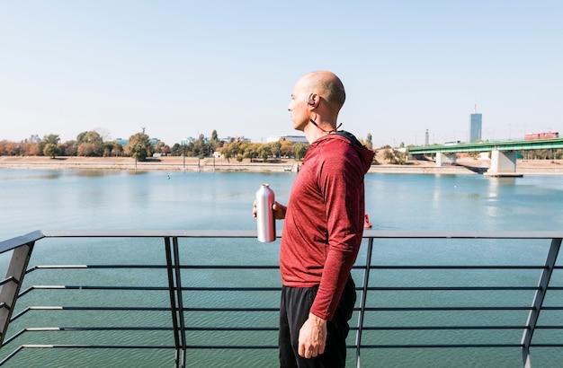 Un atleta maschio che indossa il bluetooth senza fili sul suo orecchio che tiene la bottiglia di acqua a disposizione che guarda vista Foto Gratuite