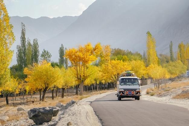 Un autobus in esecuzione su strada asfaltata lungo alberi colorati in autunno contro le montagne. Foto Premium