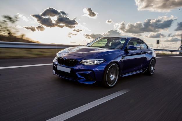 Un'automobile di berlina blu che guida sulla strada in un tempo nuvoloso. Foto Gratuite