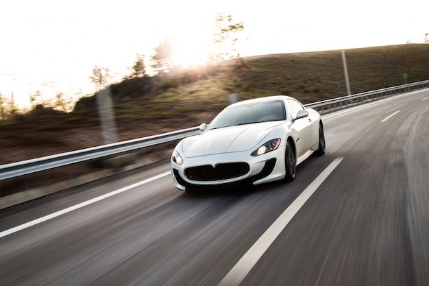 Un'automobile sportiva bianca che guida con l'alta velocità sulla strada. Foto Gratuite