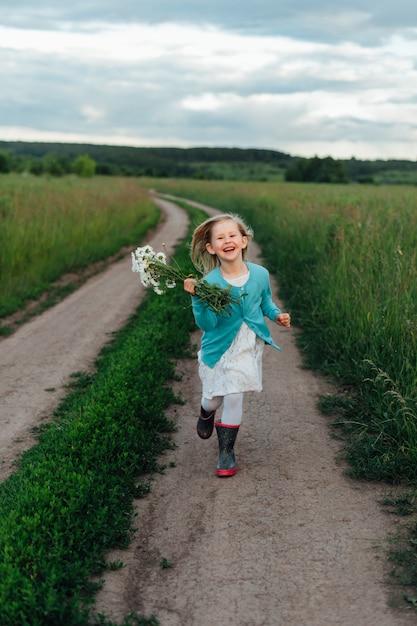 Un bambino allegro corre con un mazzo di margherite con gli stivali Foto Premium