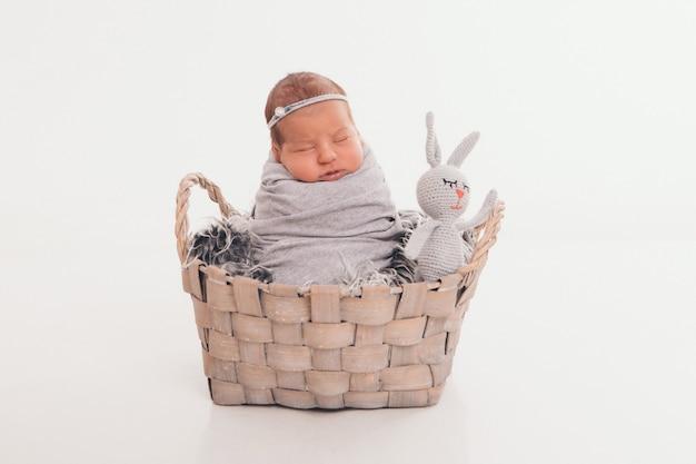 Un bambino piccolo in un cestino con giocattolo coniglio bianco. infanzia, assistenza sanitaria, fecondazione in vitro, regalo, animale. isolato su backgrpund bianco Foto Premium