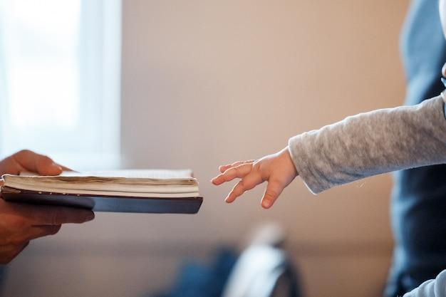 Un bambino piccolo tira la mano verso la bibbia Foto Premium