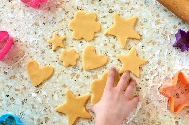Un bambino produce biscotti, stende la pasta e usa i moduli per preparare i biscotti. Foto Premium