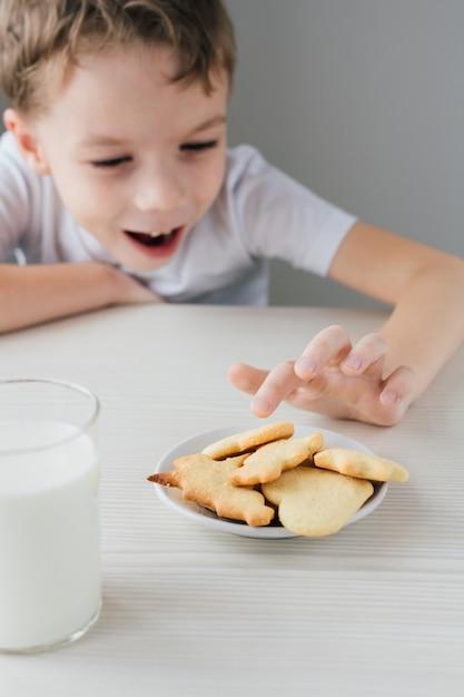 Un bambino ruba da un piatto di biscotti fatti in casa appena sfornati Foto Premium