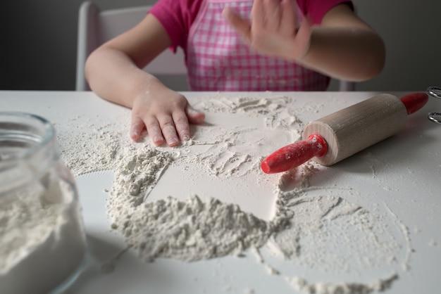 Un bambino sta giocando con la farina. la ragazza prepara i pancake. Foto Premium