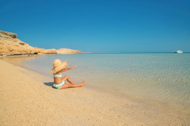 Un bambino sulla spiaggia vicino al mare. Foto Premium
