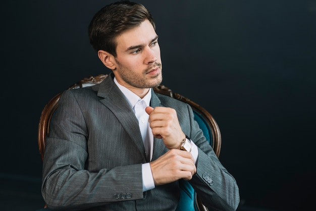 Un bel giovane attraente che si siede sulla sedia d'epoca contro sfondo nero Foto Gratuite