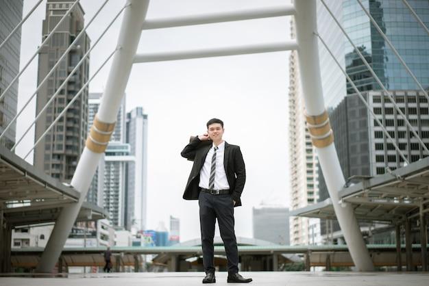 Un bell'uomo che indossa un abito nero e una camicia bianca, tiene in mano una borsetta e sta in piedi in città. Foto Premium