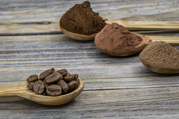 Un bello piccolo cucchiaio di legno con caffè sull'angolo differente di legno, primo piano Foto Gratuite