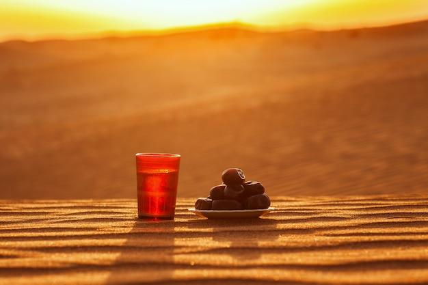 Un bicchiere d'acqua e datteri stanno sulla sabbia con vista su uno splendido tramonto. Foto Premium