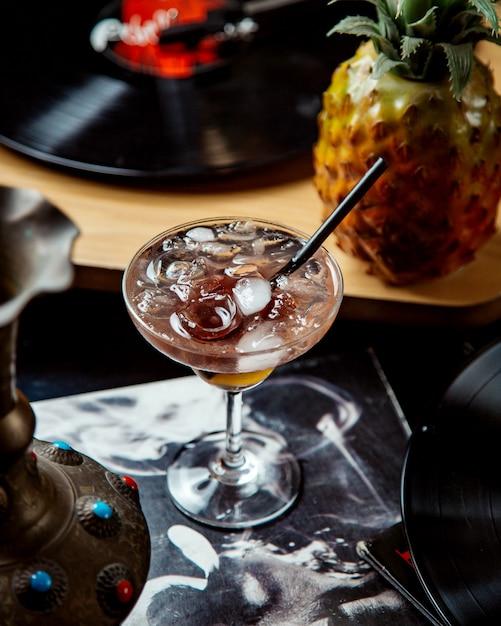 Un bicchiere di cocktail con cubetti di ghiaccio e cannuccia nera Foto Gratuite