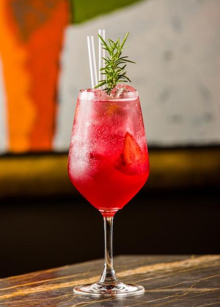 Un bicchiere di cocktail freddo alla fragola con foglie e tubi di rosmarino fresco Foto Gratuite
