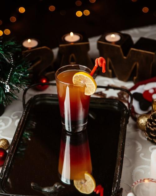 Un bicchiere di cocktail ombre guarnito con una fetta di limone attorno alle decorazioni natalizie Foto Gratuite