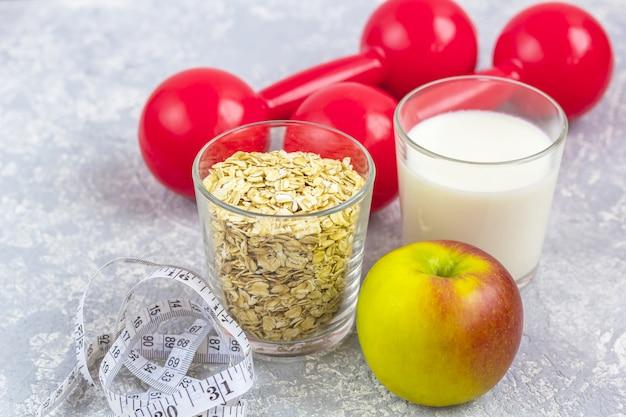 Un bicchiere di latte e un bicchiere di fiocchi d'avena (fiocchi d'avena). mela con metro a nastro e manubri. Foto Premium