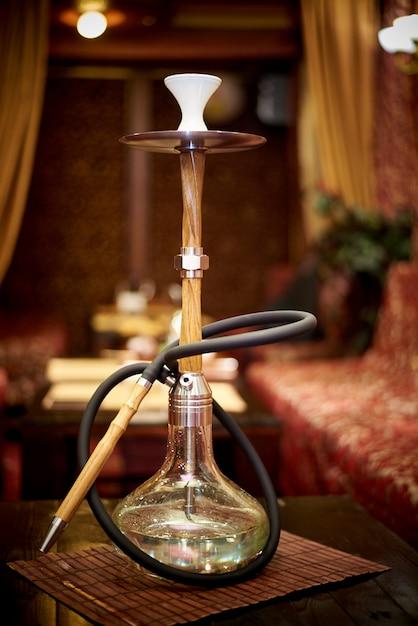 Un bicchiere di narghilè è sul tavolo nel lounge bar Foto Premium