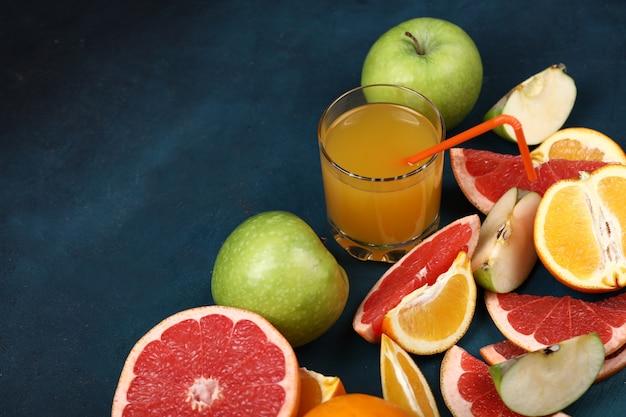Un bicchiere di succo d'arancia con frutta tropicale a fette. Foto Gratuite