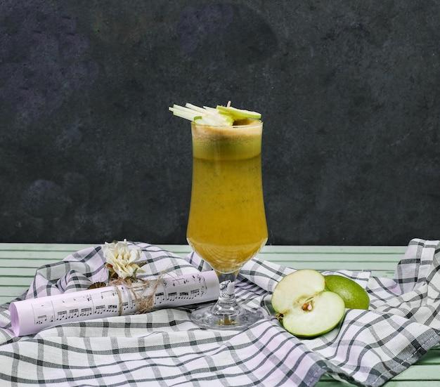 Un bicchiere di succo di mela cocktail su un pezzo di legno. Foto Gratuite