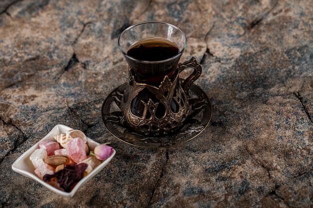 Un bicchiere di tè con noci e dolci in un piattino bianco Foto Gratuite