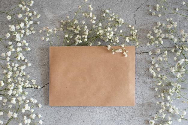 Un biglietto di auguri a tema invernale mock up con busta d'oro e ornamenti. Foto Premium
