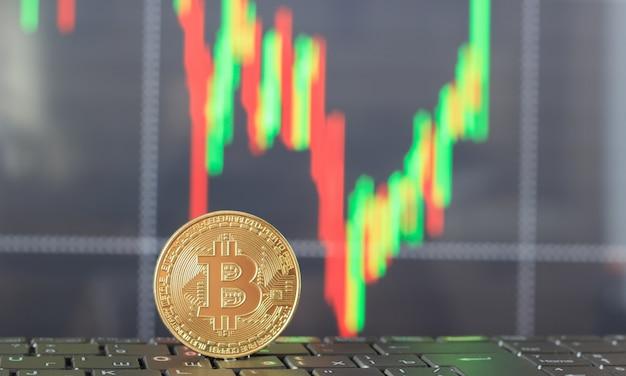 Un bitcoin sulla tastiera e un grafico della crescita e del calo dei prezzi Foto Premium