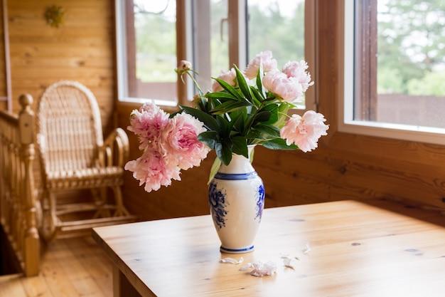 Un bouquet di peonie primaverili in un vaso su un tavolo su un'accogliente terrazza. Foto Premium