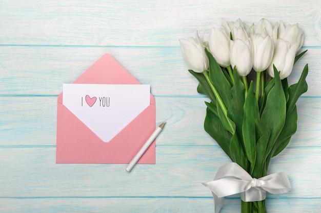 Un bouquet di tulipani bianchi con nota d'amore e busta di colore su tavole di legno blu Foto Premium
