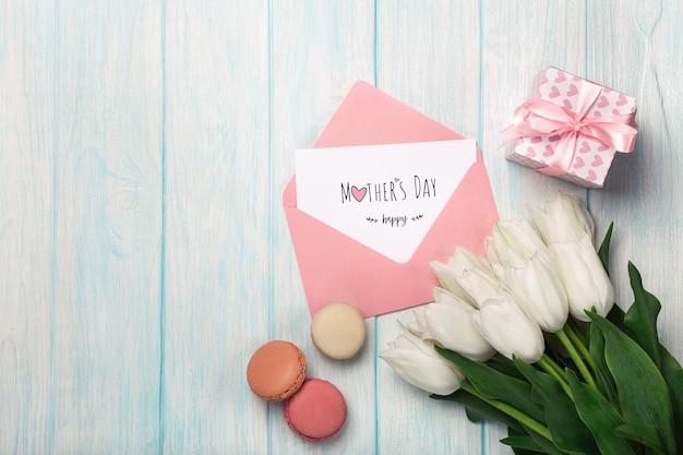 Un bouquet di tulipani bianchi con una confezione regalo, macarons, note d'amore e busta colorata su assi di legno blu. festa della mamma Foto Premium