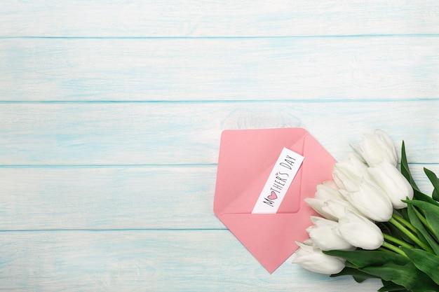Un bouquet di tulipani bianchi con una nota di amore e busta di colore su tavole di legno blu. festa della mamma Foto Premium