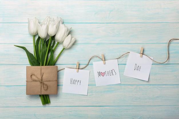 Un bouquet di tulipani bianchi e busta con adesivi con mollette su una corda e tavole di legno blu. festa della mamma Foto Premium