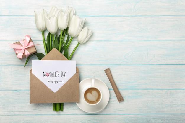 Un bouquet di tulipani bianchi, tazza di caffè, confezione regalo con una nota d'amore e busta su tavole di legno blu. festa della mamma Foto Premium
