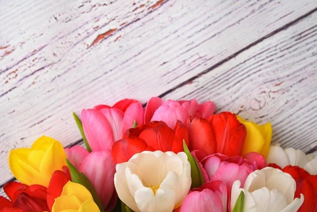 Un bouquet di tulipani freschi, luminosi e multicolori su assi di legno bianchi. Foto Premium