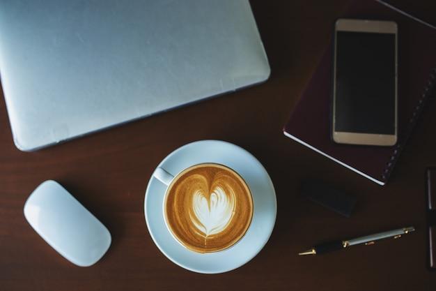 Un caffè latte e un computer portatile sul tavolo. Foto Premium