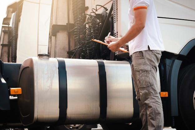 Un camionista che tiene appunti il suo controllo quotidiano della sicurezza un grande serbatoio di carburante di semi camion. trasporto merci. Foto Premium