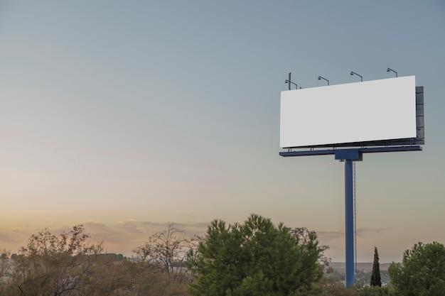 Un cartellone pubblicitario vuoto contro il cielo blu Foto Gratuite