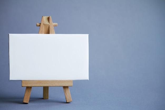 Un cavalletto in miniatura con un bordo bianco per la scrittura, puntatore sulla superficie bianca Foto Premium