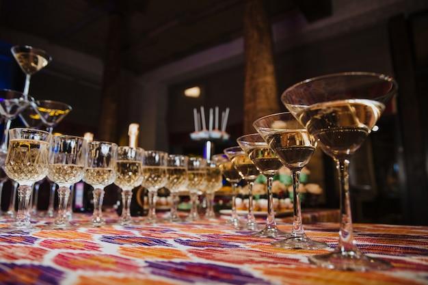 Un certo numero di bicchieri di bevande sul tavolo del ristorante Foto Premium