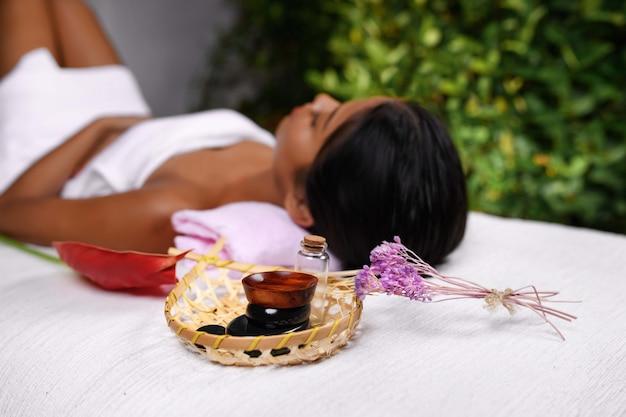 Un cesto con oli aromatici e un rametto di fiori. ragazza interrazziale in un asciugamano su un lettino da massaggio Foto Premium