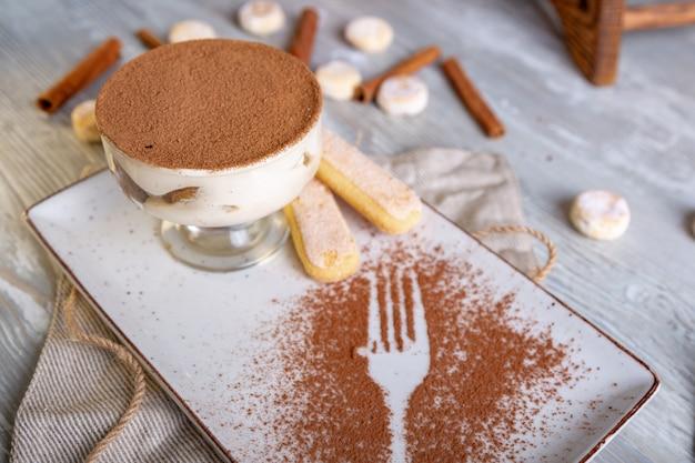 Un classico tiramisù dolce italiano in una ciotola con una porzione atmosferica di tè. Foto Premium