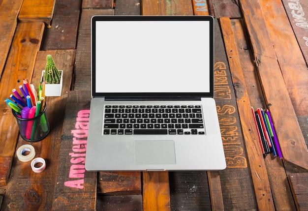 Un computer portatile aperto con le cancellerie sulla scrivania di legno dell'ufficio Foto Gratuite